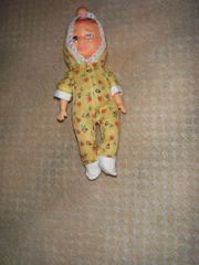 kleine Puppe mit gelben Strampler